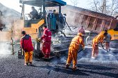 stock photo of tar  - Workers making asphalt with shovels at road constructio - JPG