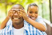 playful african girl covering boyfriend's eyes with hands