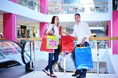 pic of mall  - happy young couple with bags in shopping centre mall - JPG