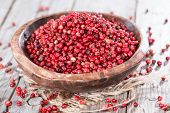 stock photo of peppercorns  - Small portion of dried Pink Peppercorns  - JPG