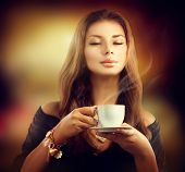 Coffee. Beautiful Woman Drinking Tea or Coffee in Cafe. Beauty Model Girl with the Cup of Hot Bevera