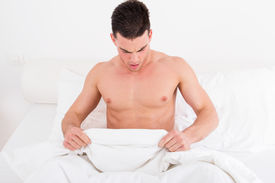pic of half naked  - surprised half naked young man in bed looking down at his underwear at his penis under white covers sheet in badroom - JPG