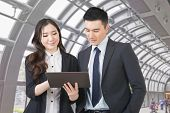 Business man and woman hold a tablet and discuss, closeup portrait with copyspace.