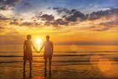 Young couple on the beach during amazing sunset. Honeymoon.