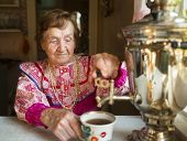 Grandmother in a rural house drinking tea from a Russian samovar.