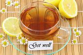 Get well card with cup of chamomile tea and lemon on bamboo mat