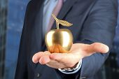 Businessman standing and holding golden apple in his hand.
