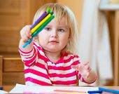 Cute three-year-old girl draws felt-tip pens at home