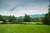 image of asheville  - A grassy lawn stretches out in front of a distant view of the Blue Ridge Mountains - JPG