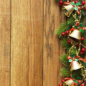 Decorated Christmas tree border on wood paneling with gold baubles and bells, a decorative Xmas gift