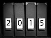 Four black binders with New Year 2015 digits placed on bookshelf