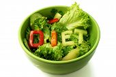 Green plate with word diet composed of slices of different vegetables on salad