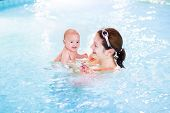 Cute Newborn Baby Having Fun In A Swimming Pool With His Mother