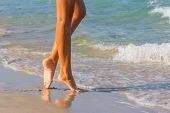 Female leg walking on the beach in the ocean - Narrow depth of field