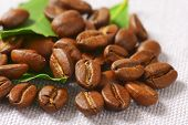 roasted coffee beans with green leaves, scattered on the tablecloth