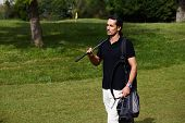 Attractive male golfer walking to the next hole in golf course