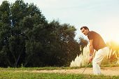 Strong golf shot of handsome player standing on golf course