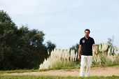Wealthy man in sport clothes holding golf driver walk
