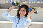 Goofy girl holding a skateboard on her head