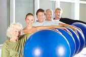 Group of seniors doing fitness training with gym balls in rehab center