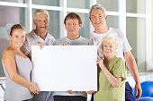 Group of happy senior people holding white empty cardboard sign in gym