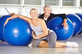 Two happy senior people sitting in gym with exercise ball