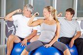 Senior group doing dumbbell training in gym while sitting on exercise balls