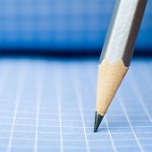 Sharp wooden pencil on blue checkered paper