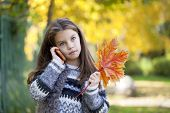 Beautiful young school girl talking on mobile phone in the autumn park
