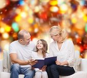 family, childhood, holidays and people - smiling mother, father and little girl reading book over re