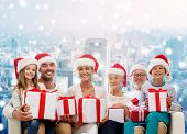 family, happiness, generation, holidays and people concept - happy family in santa helper hats with