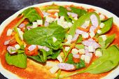 raw pizza with spinach and tomato sauce