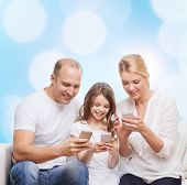 family, holidays, technology and people concept - smiling mother, father and little girl with smartp