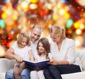 family, childhood, holidays and people - smiling mother, father and little girls reading book over r
