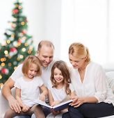 family, childhood, holidays and people - smiling mother, father and little girls reading book over l