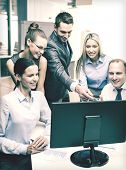 business, technology and office concept - smiling business team with computer monitor having discuss
