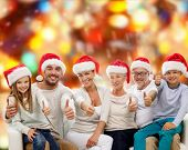 family, generation, gesture, holidays and people concept - happy family in santa helper hats showing