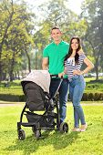 Vertical shot of young parents posing with their baby in a park on a sunny day