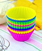 stock photo of cake-mixer  - Colorful silicone molds for cakes, mixer, yellow cloth potholder, the dough in a glass bowl on linen background