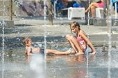 Children Playing In Puddle On Hot Weather