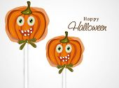 Smiling pumpkin face lollipop for Halloween party and day celebration on beige background.