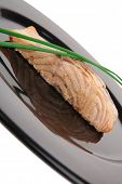 healthy fish cuisine : baked pink salmon steaks with green onion on black dish isolated over white background