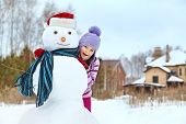 kid playing with snowman