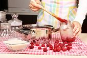 Woman cooking raspberry jam in kitchen