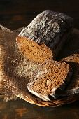 Sliced rye bread on sackcloth napkin on wicker basket on wooden background