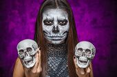 Young Woman In Day Of The Dead Mask Skull Face Art With Two Skulls In Hands.