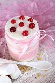 Raspberry milk dessert in glass jar, on color wooden  table background