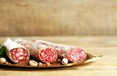 Italian salami on tray, on wooden background