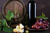 Wine in bottle and in goblet, Camembert cheese, grapes and wooden barrel on wooden table on wooden b