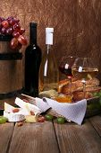 Supper consisting of Camembert and Brie cheese, wine and grapes on napkin in basket and wine barrel on wooden table on brown background